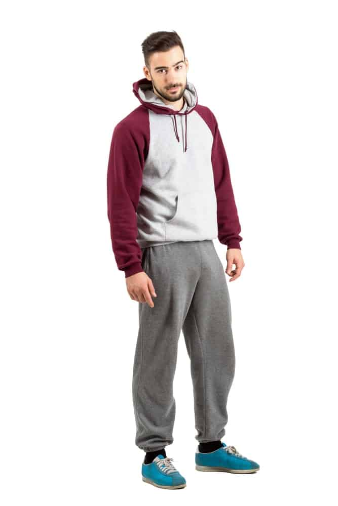 A serious man wearing gray, baggy sweatpants