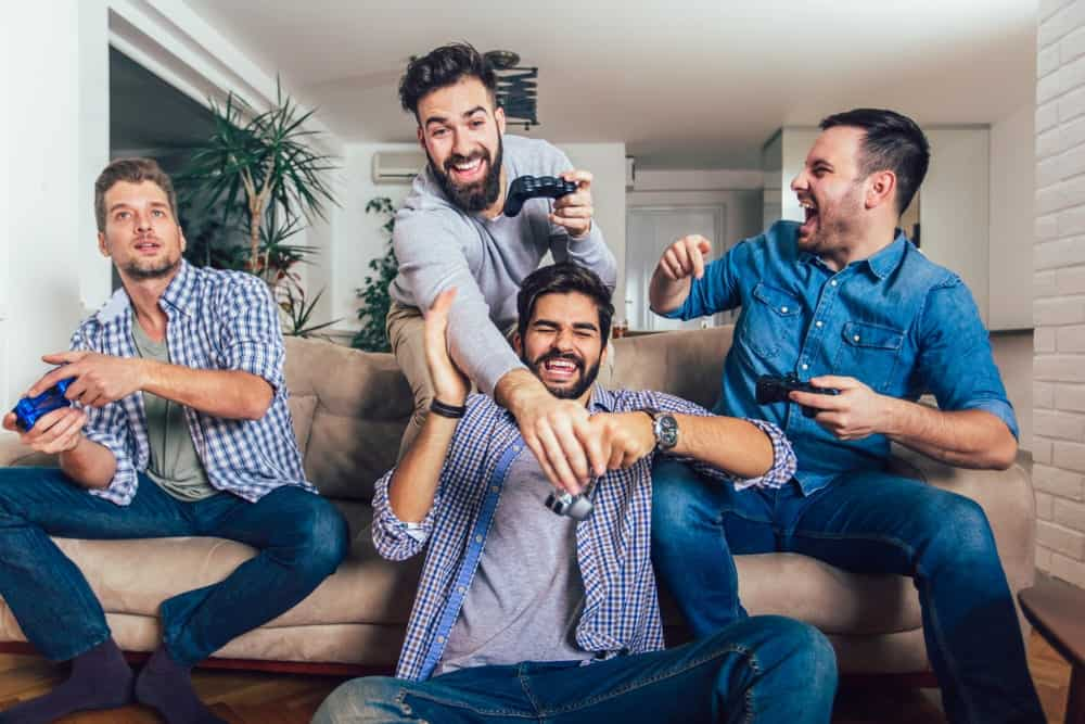 A group of young men having fun while playing a video game.