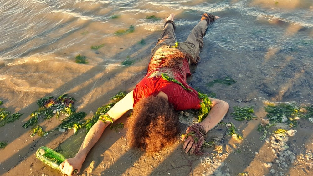 A castaway lays on the seashore face down.