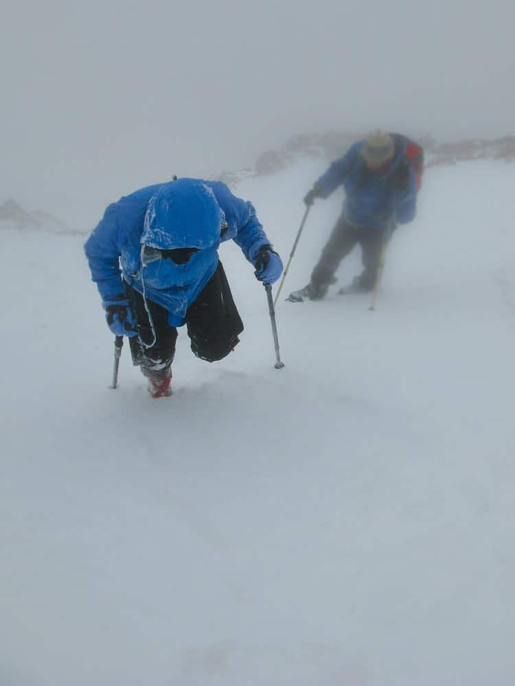 Two climbers struggle against the blizzard storm.