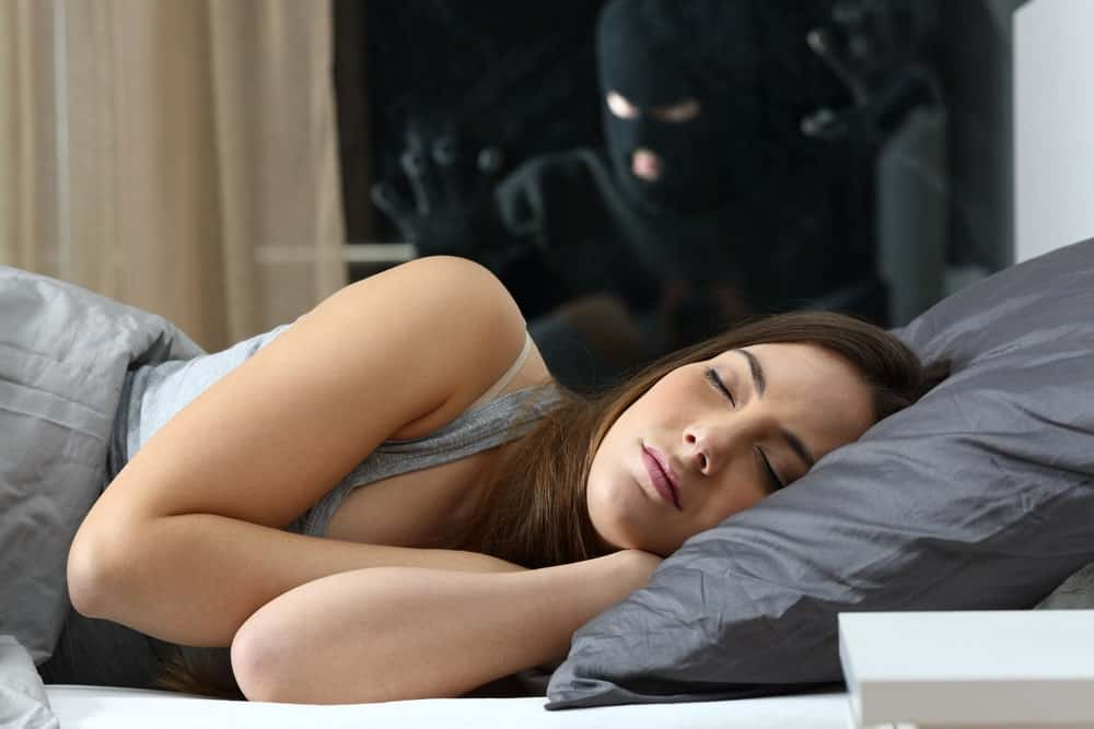 A man in black hood tries to enter the bedroom window as a woman lays asleep.