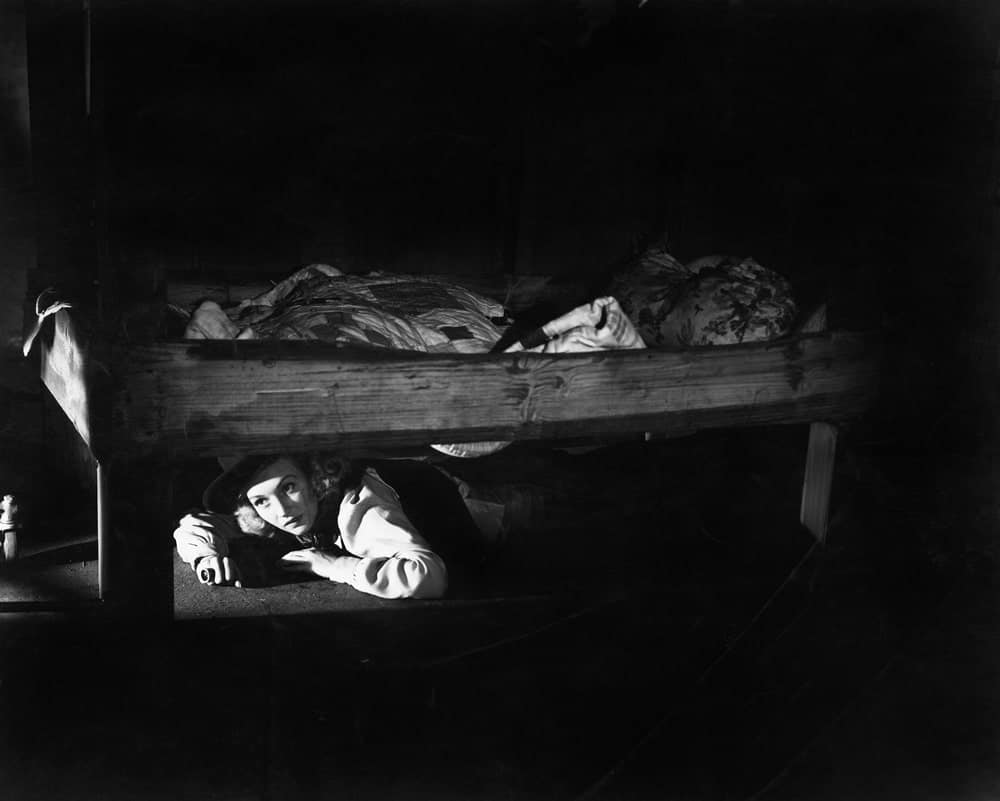 A woman hiding under the bed in the dark.