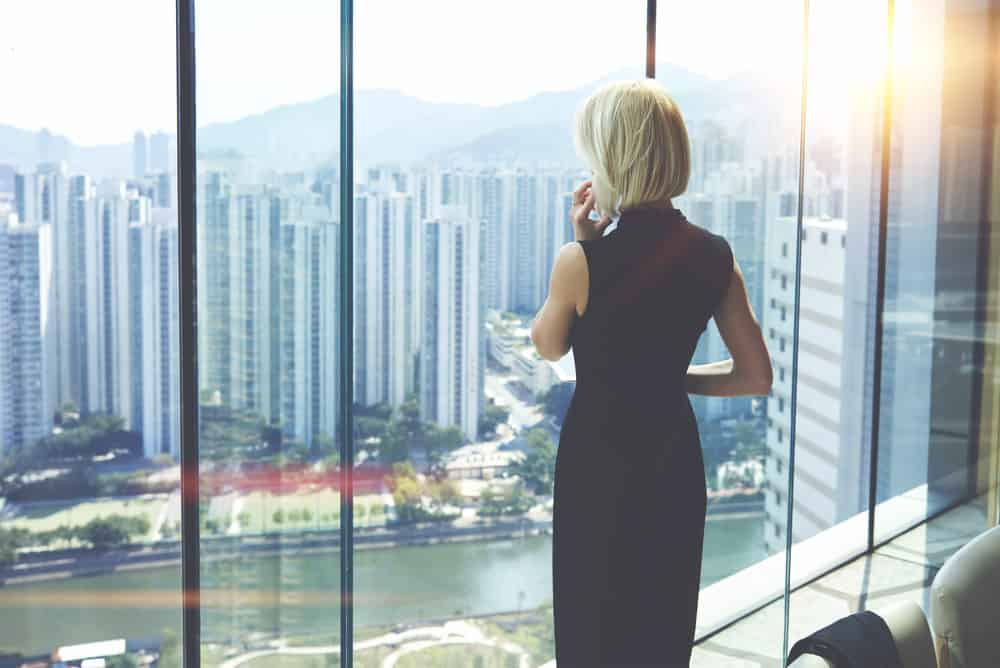 Woman CEO in skyscraper office with killer views