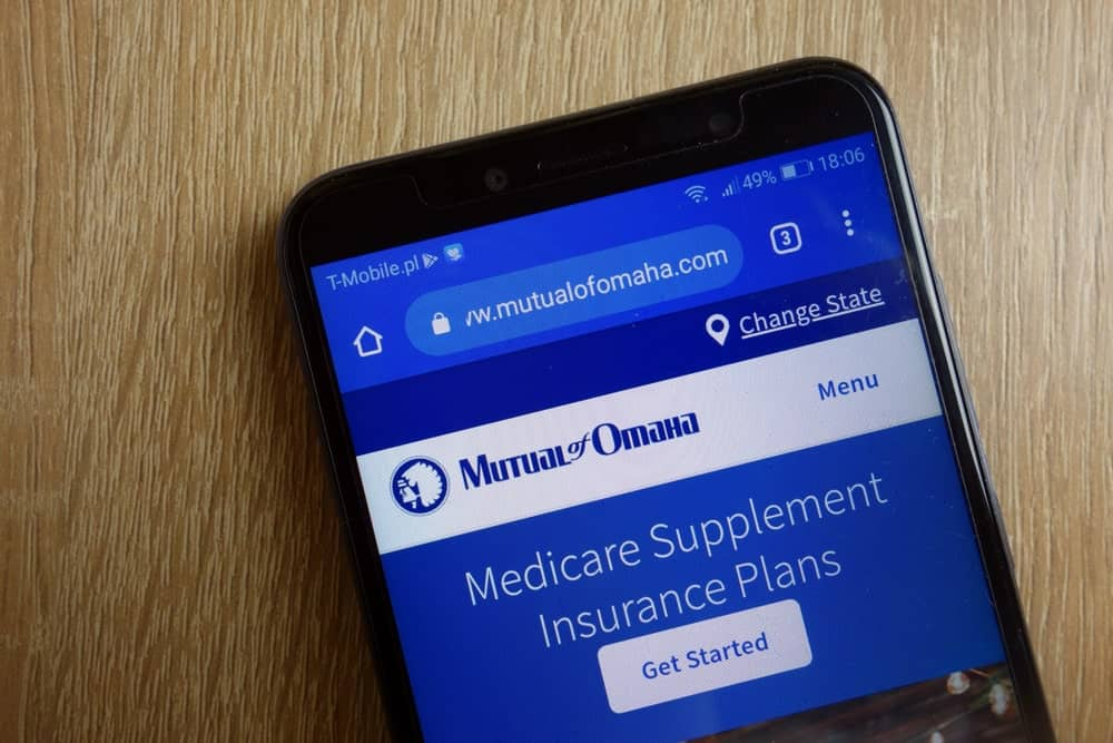 Mutual of Omaha Insurance Company mobile website homepage shown on a smartphone against a wooden background.