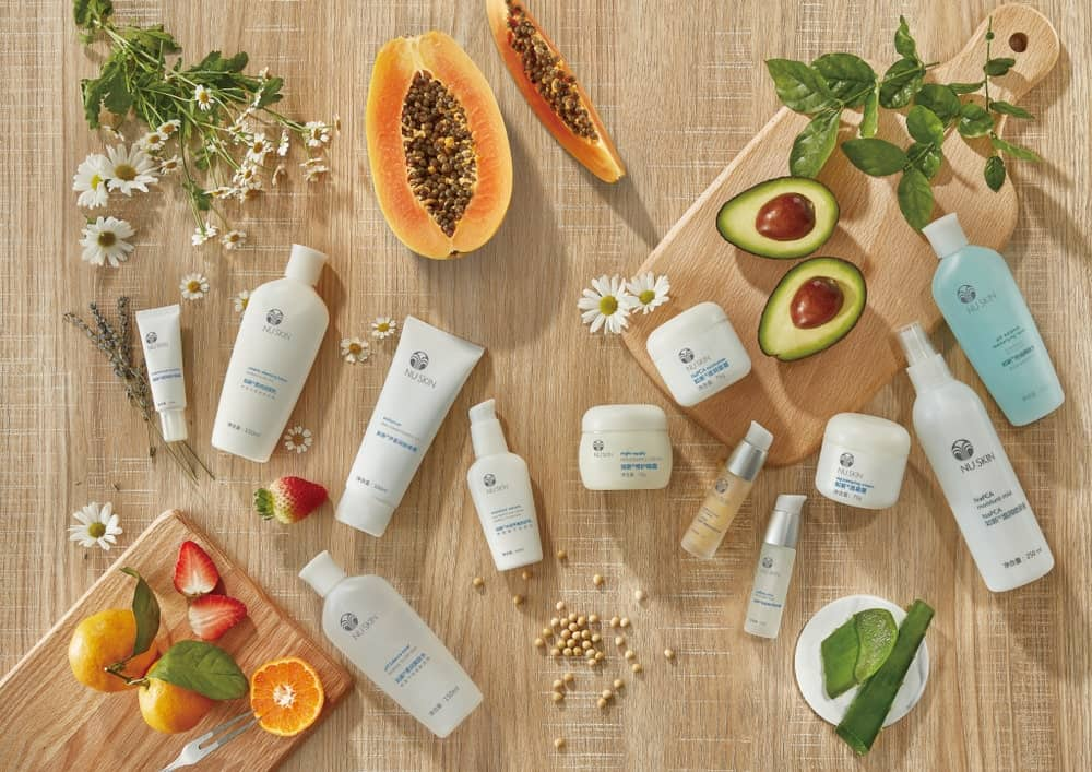 NuSkin products mixed with fruits, flowers, and plants on a wooden background.