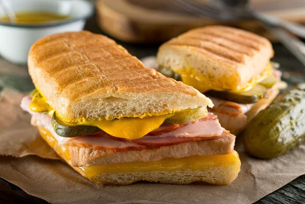 Cuban sandwiches beside a pickle.