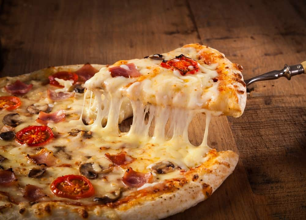 Getting a slice of pizza with melting cheese.