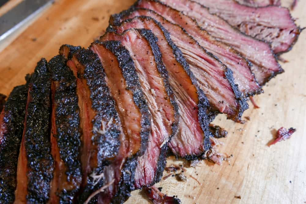 Sliced smoked brisket on a cutting board.