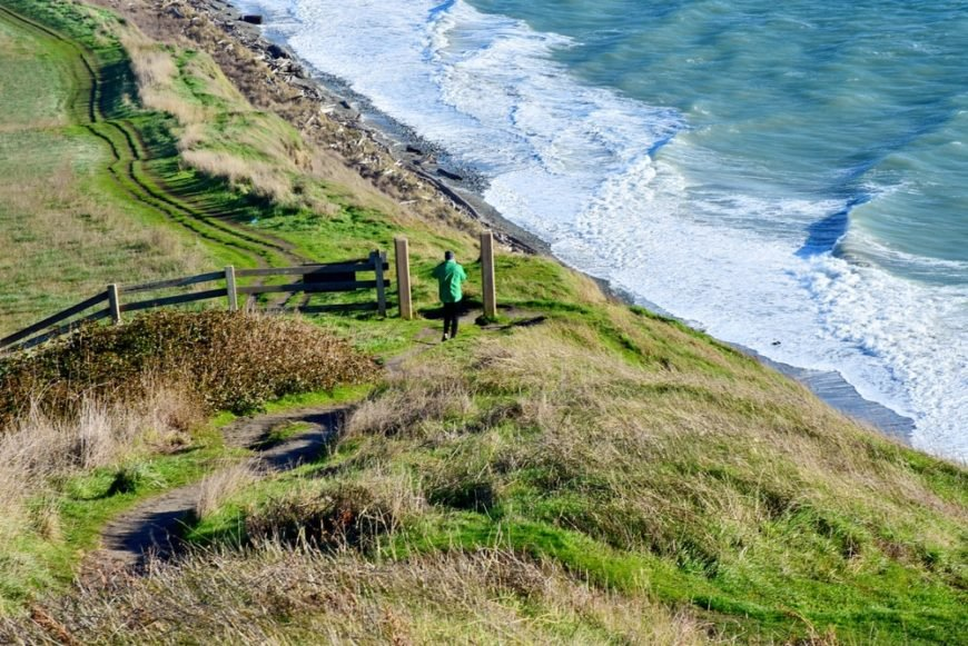 A man passing a hiking trail in Whidbey Island, WA.