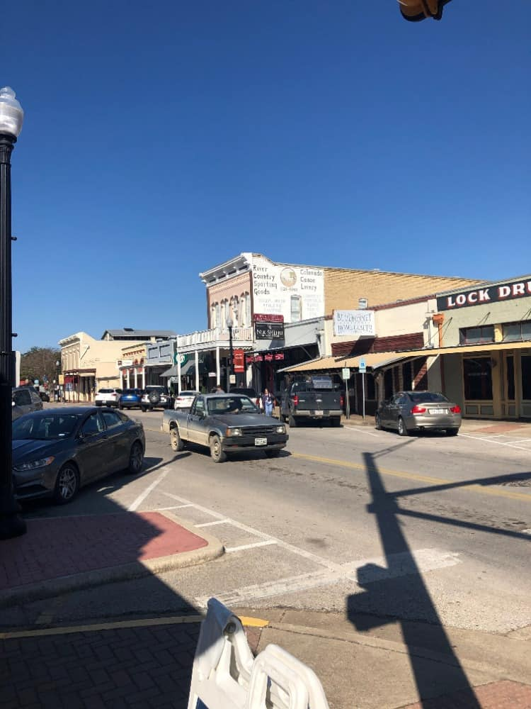 Busy time at the Downtown Bastrop, cars driving around. There are parked cars everywhere too.