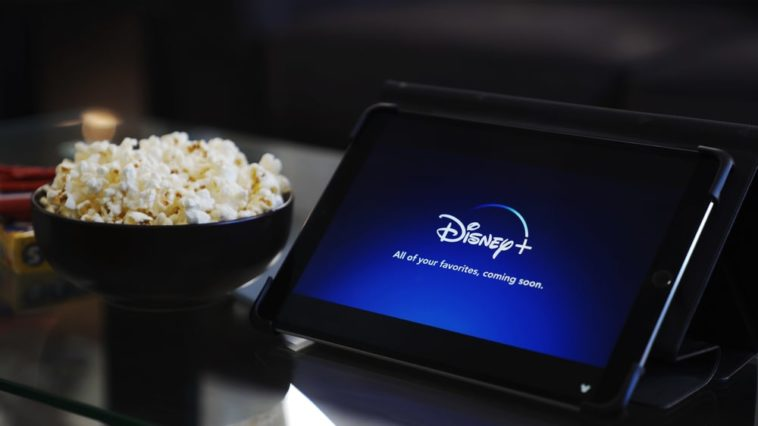 A tablet showing the Disney+ logo beside a bowl of popcorn.