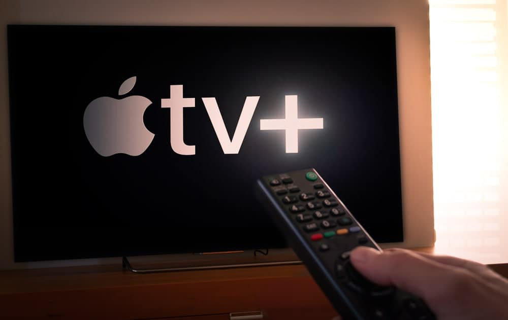 Man with a remote control turns the channel to Apple TV+.