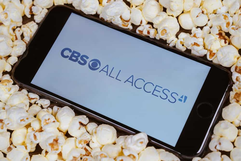 CBS All Access displayed on a smartphone screen against a bunch of popcorn.