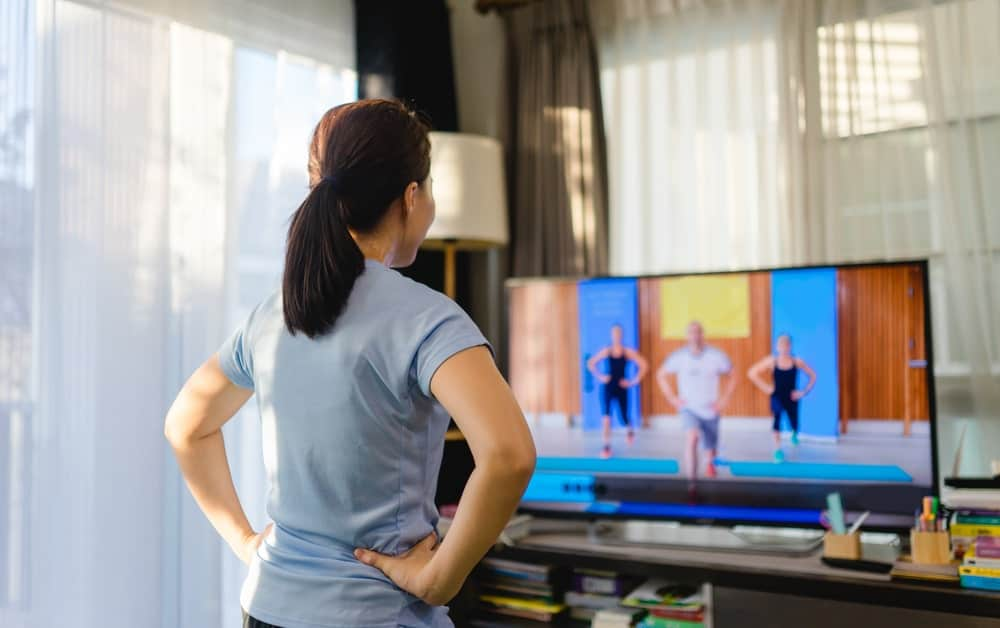 Woman doing aerobics as she watches a livestream of a fitness workout class.