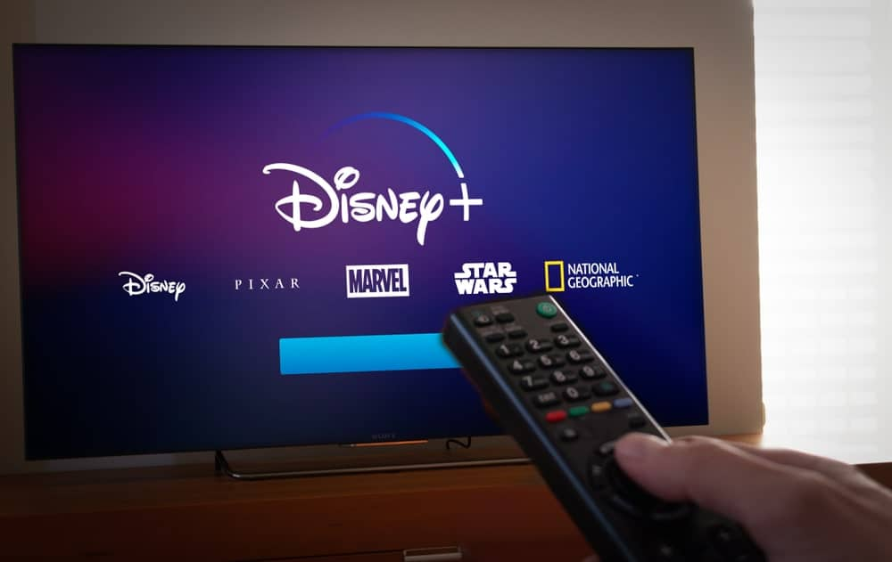 A hand using the remote on a TV that shows the Disney+ logo along with its various content.