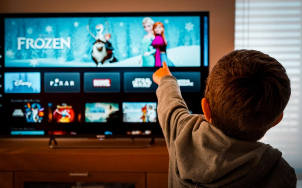 A child pointing at the TV that shows the home screen for Disney+.