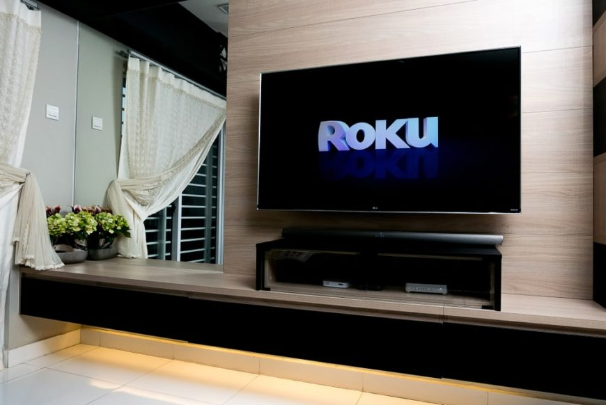A wall-mounted smart TV showing the logo for Roku.