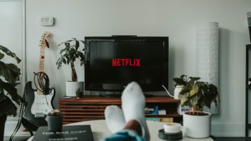 A person relaxing while watching Netflix on the TV.