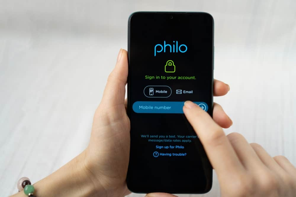 Woman holding a smartphone with Philo application.