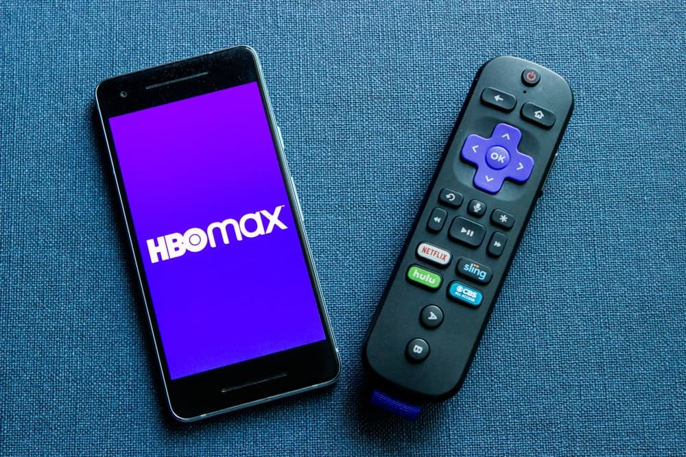 A mobile phone with the HBO Max logo and a Roku remote.