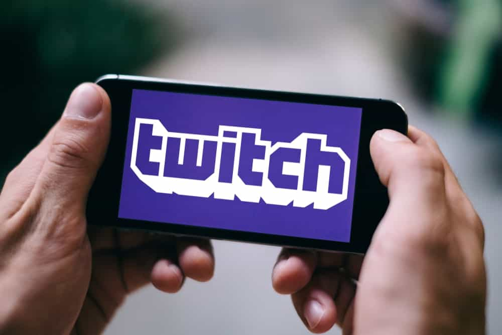 Hands holding a smartphone that displays twitch logo.