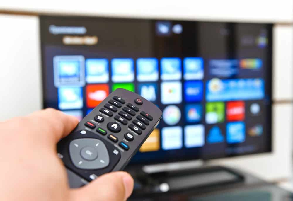 A close look at a hand pointing the remote to the smart TV.