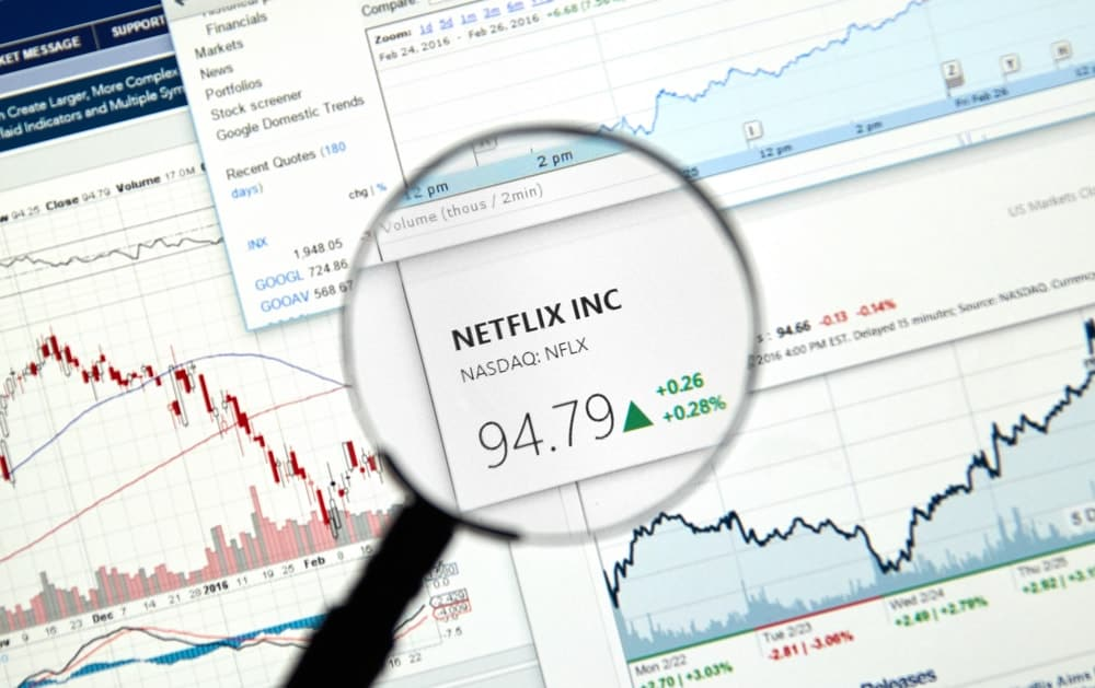 This is a close look at the stock market ticker of Netflix Inc. surrounded by graphs and tables.