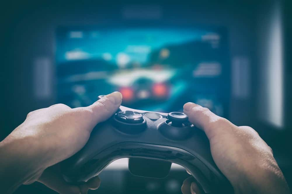 A close look at a pair of hands on a video game controller while playing a racing game.