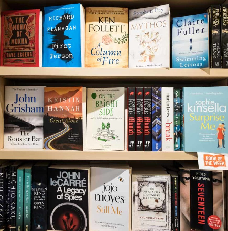 A bookshelf display in a bookstore featuring various authors including Kristin Hannah.