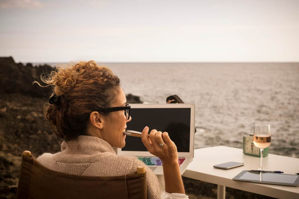 A writer with her laptop by the sea.