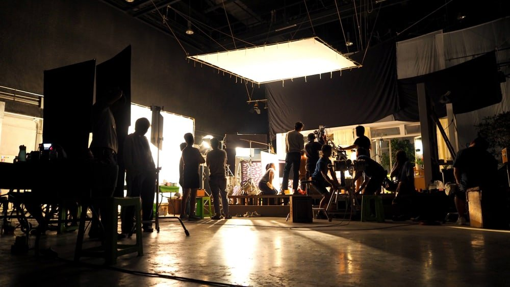 This is a view of behind the camera at a film shooting showcasing multiple film crews working behind the scenes.