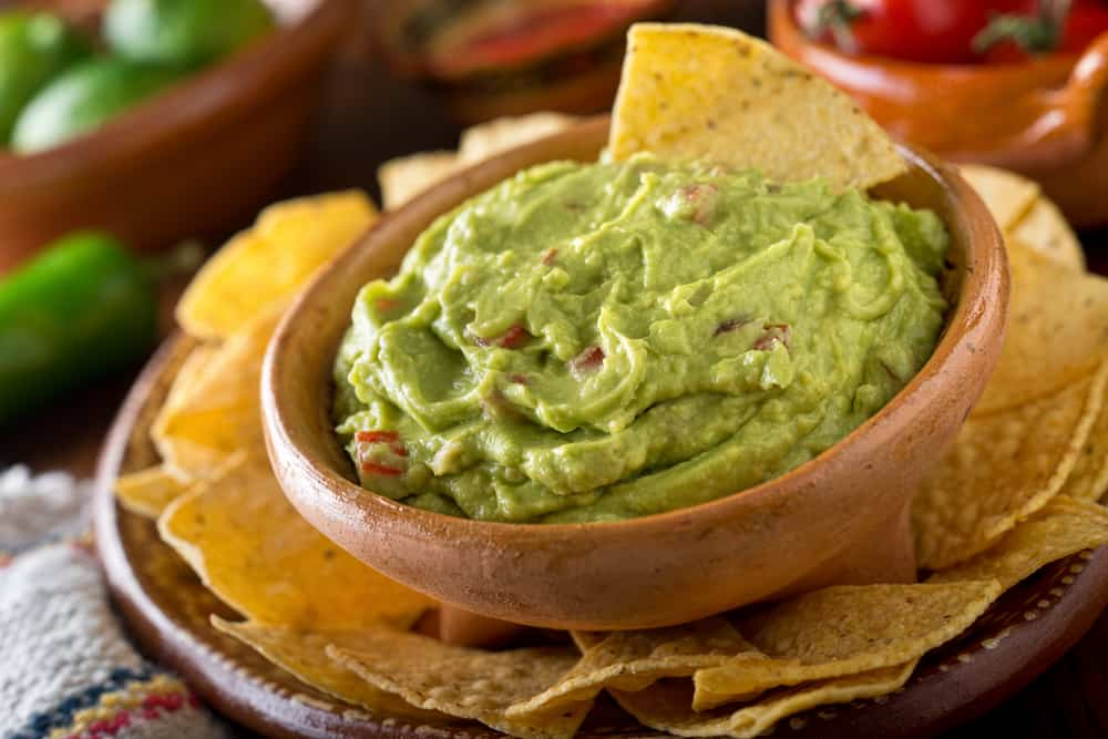Guacamole dip with avocado, lime, and tomato surrounded by nacho chips.