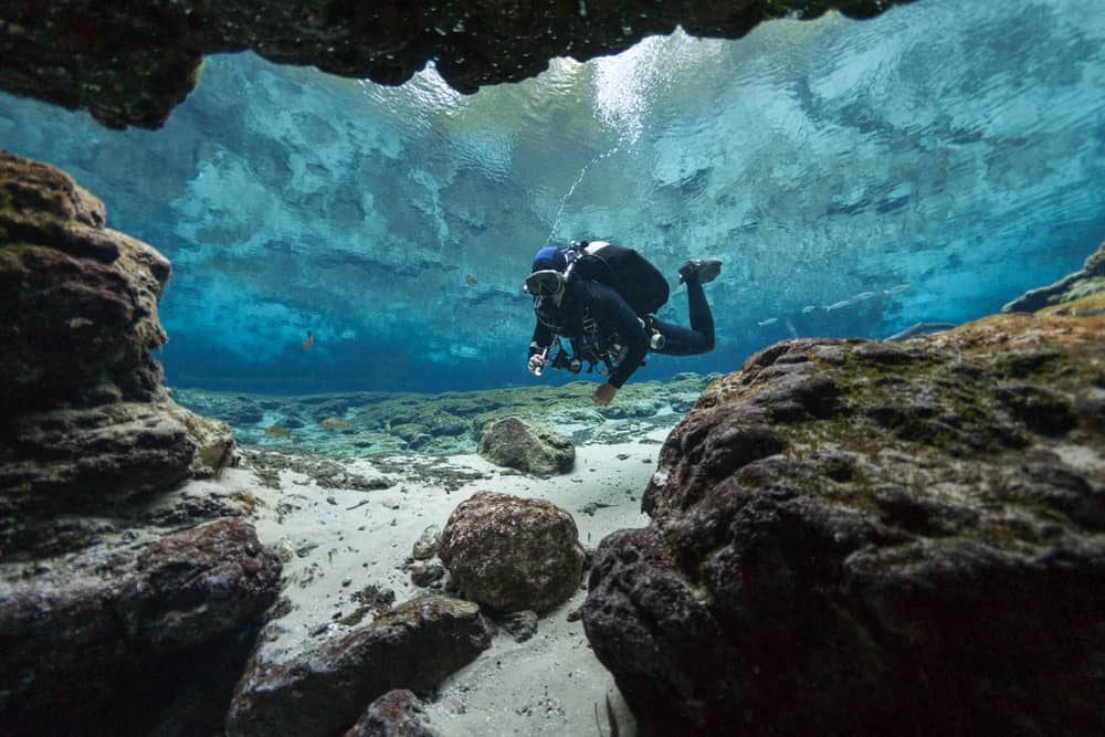 This is a close look at a diver at the bottom of an underwater cave with rocks and boulders.