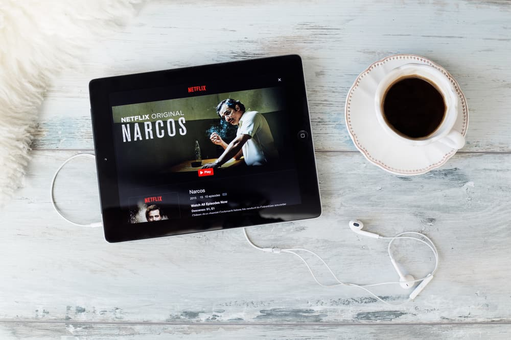 A tablet showcasing the Narcos homepage in Netflix on a table with a cup of coffee.
