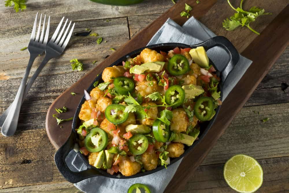 Mexican tater tot nachos with cheese, cilantro and jalapeño.