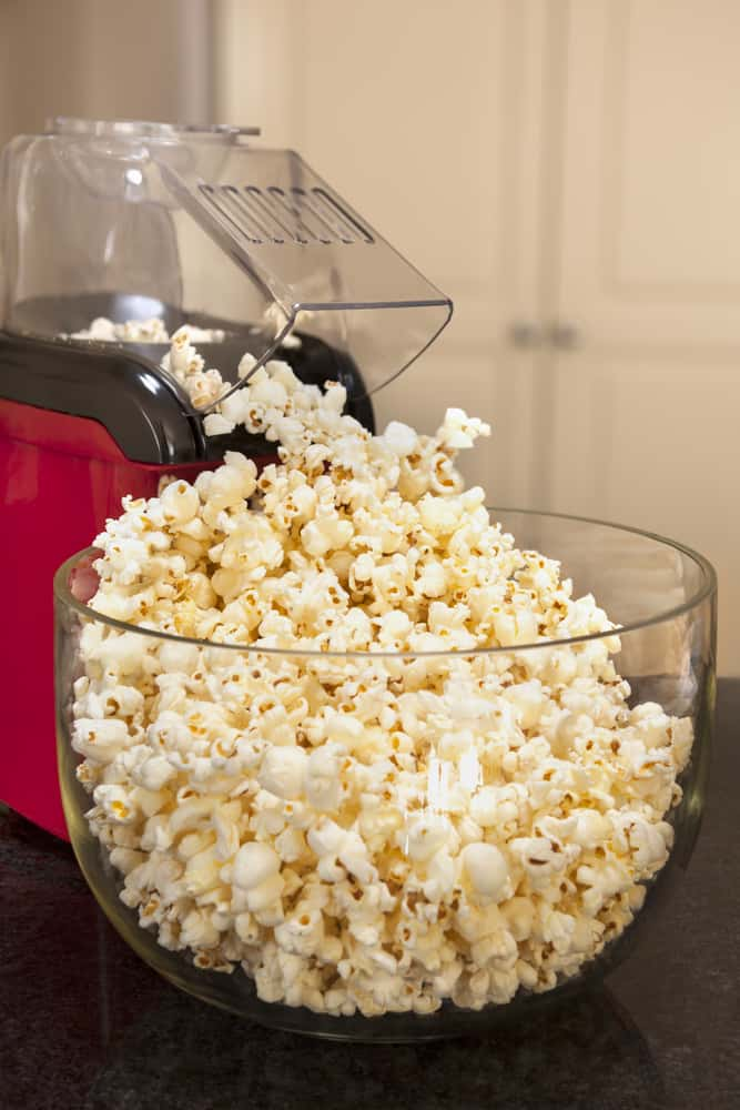 A large glass bowl filled with freshly-made popcorn.