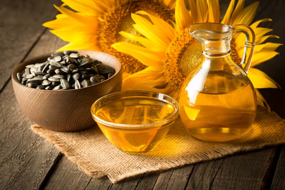 Sunflower oil in a glass jar and in a glass bowl beside a bowl of sunflower seeds.
