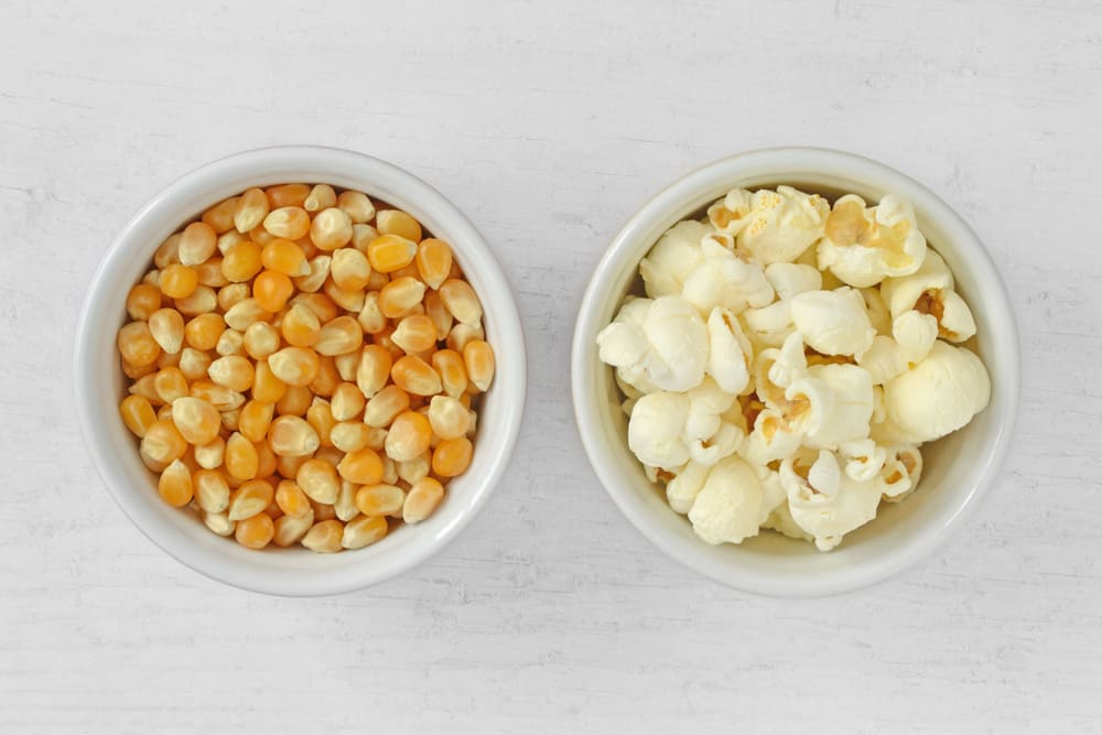 This is a look at a bowl of yellow popcorn kernels and a bowl of yellow popcorn.
