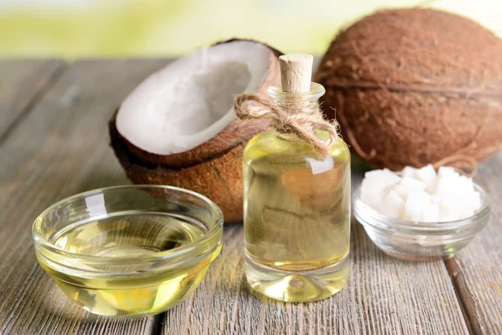 Various types of coconut oil with fresh coconuts on a wooden table.