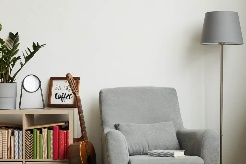 This is a close look at a gray cushioned Lawson chair paired with a gray standing lamp.