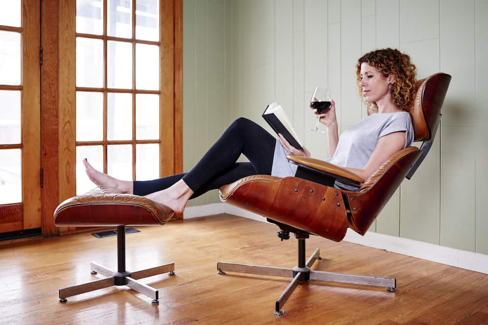 A woman reading a book on an Eames Lounge Chair with a matching footstool.