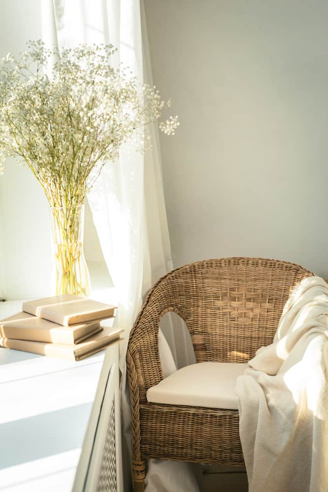 This is a close look at a reading nook by the window with a woven wicker tub chair that has a cushion.