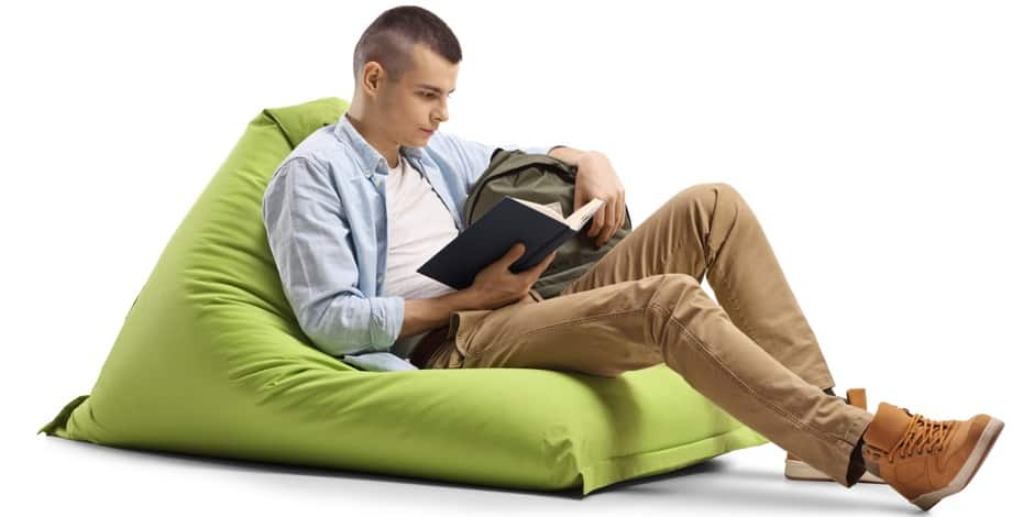 A man reading a book while sitting on a green bean bag chair.