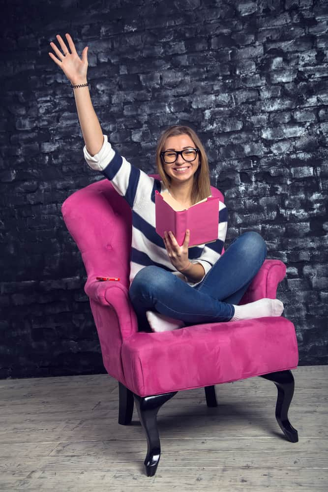 A woman reading a pink book on a pink club chair.