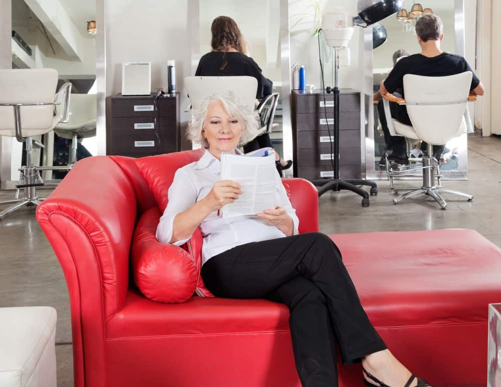 A woman reading a book on a red leather chaise lounge.