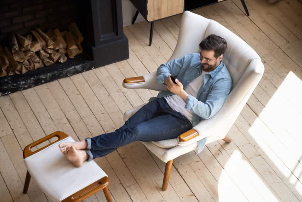 A man browsing his phone while sitting on a lounge chair with foot stool by the fireplace.