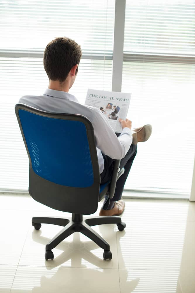 A man reading the newspaper on a swiveling blue office chair with wheels.