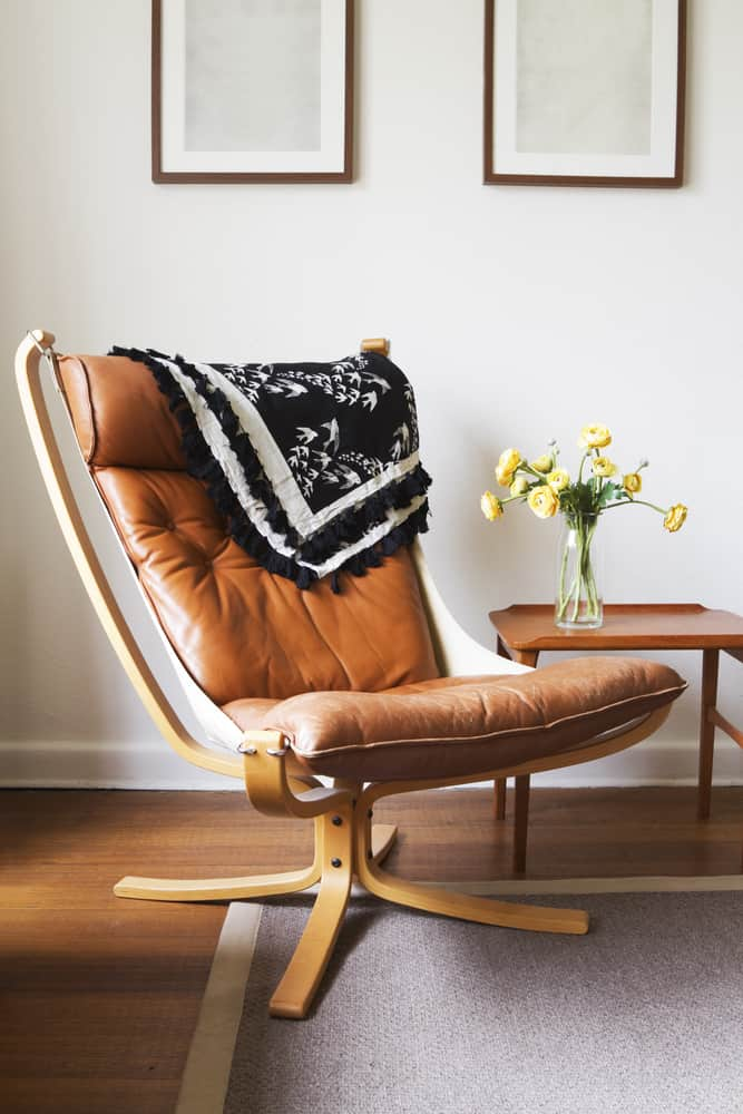 This is a close look at a reading nook with a vintage tan slipper chair and a side table.