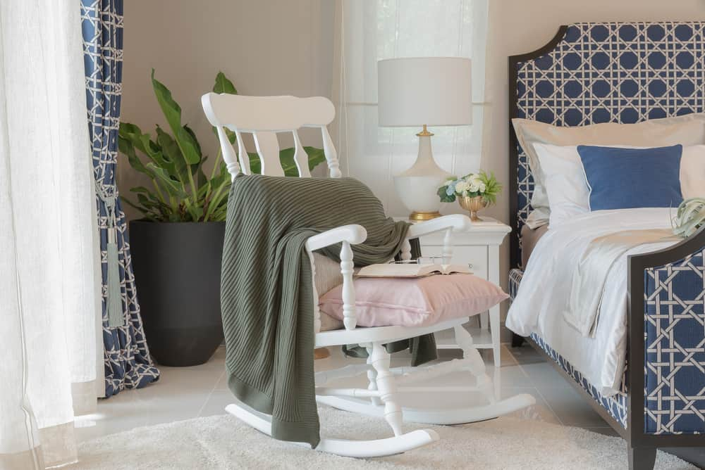 This is a close look at the bedroom with a white wooden rocking chair on the side to act as reading area.