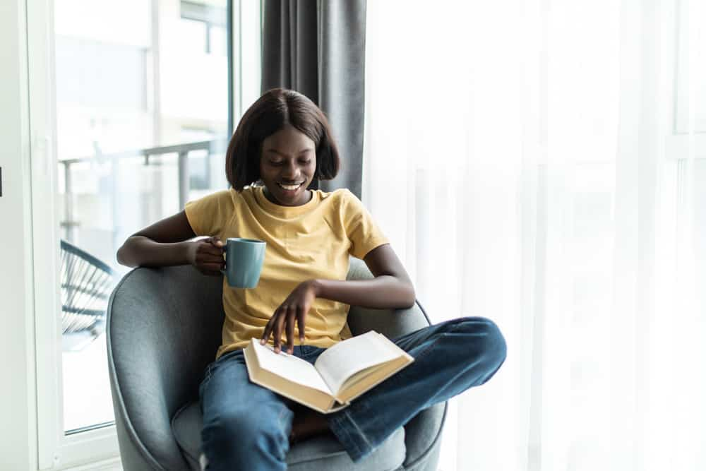 This is a look at a woman reading a book on a barrel chair by the window.